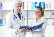 Doctor checking medical records. Confident doctor in the office checking medical records with his assistant, healthcare and teamwork concept Stock Photography