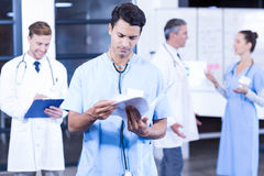 Doctor checking medical report in hospital. Doctor checking medical report  while his colleagues discussing in background Royalty Free Stock Image