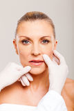 Lips plastic surgery. Doctor checking middle aged woman lips before plastic surgery Stock Image