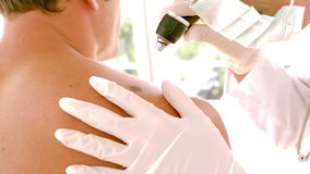 Doctor checking a mole on patient stock footage
