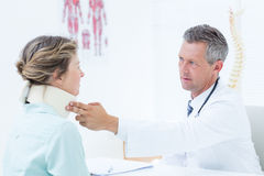 Doctor checking neck brace of his patient Stock Image