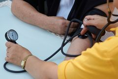 Doctor checking old woman patient arterial blood pressure, close-up. Taking pulse of the elderly woman patient, outdoors. Woman`s health check blood pressure stock image