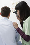 Doctor Checking Patient Ear's With Otoscope Royalty Free Stock Photography