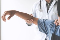 Doctor checking patient with elbow to determine the cause of ill stock images