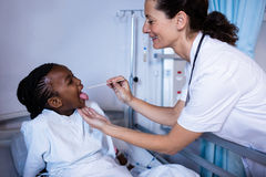 Doctor checking patient fever from thermometer during visit in ward. At hospital Stock Photos