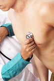 Doctor checking patient heart beat Stock Image