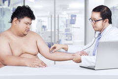 Doctor checking the patient heartbeat royalty free stock photo