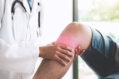 Doctor checking patient with knees to determine the cause of ill stock photography