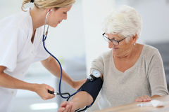 Doctor checking on patient's blood pressure Stock Photos