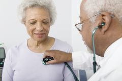 Doctor Checking Patient's Heartbeat Using Stethoscope. An African American senior male doctor checking patient's heartbeat using stethoscope Stock Images