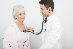Doctor Checking Patient's Heartbeat Using Stethoscope. A happy male doctor checking patient's heartbeat using stethoscope at clinic Stock Image