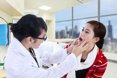 Doctor checking patient throat Stock Photo