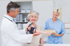 Doctor checking patients blood pressure while nurse noting it Royalty Free Stock Image