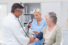 Doctor checking patients blood pressure while nurse noting it Royalty Free Stock Photos
