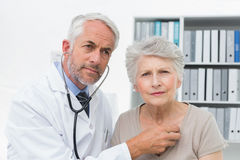 Doctor checking patients heartbeat using stethoscope Royalty Free Stock Photo