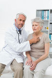 Doctor checking patients heartbeat using stethoscope Stock Photos