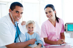 A doctor checking the pulse on a little girl. A doctor checking the pulse on a smiling little girl in the hospital Royalty Free Stock Image