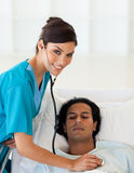 Doctor checking the pulse of a patient. Female doctor checking the pulse of a patient in the hospital Royalty Free Stock Image