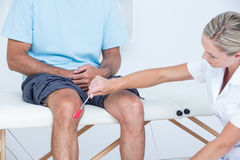 Doctor checking reflexes of the knee of her patient Stock Image