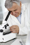 Doctor checking sample thorugh microscope Stock Images