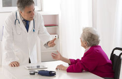 Doctor checking senior female patient's injured arm Royalty Free Stock Photo