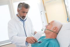 Doctor checking on senior patient heart rate. Checking royalty free stock photo