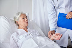 Doctor checking senior woman pulse at hospital Stock Photography