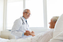 Doctor checking senior woman pulse at hospital Royalty Free Stock Photography