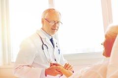 Doctor checking senior woman pulse at hospital Stock Photo