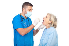 Doctor checking for sore throat Stock Images