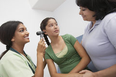 Doctor Checking Teenage Girl's Ear. Happy female doctor checking girl's ear as she to the patient's mother royalty free stock images