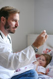 Doctor checking temperature of little patient. Stock Images
