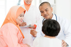Doctor checking temperature of sick children Stock Photos