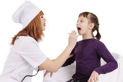 Doctor checking the throat of a young patient girl over white Stock Images