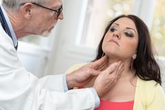 Doctor checking thyroid Royalty Free Stock Photography
