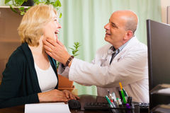Doctor checking thyroid of  woman Stock Photo