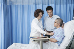 Doctor checking up on patient who is lying down in bed with adult son by his side Royalty Free Stock Images