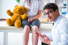 The doctor checking up young girls reflexes with hammer stock photography