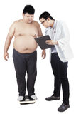 Doctor checking the weight of patient Royalty Free Stock Photography