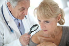 Doctor checking woman's skin Stock Photography