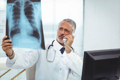 Doctor checking a x-ray report while talking on phone Royalty Free Stock Photo