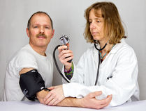 Doctor checks blood pressure of a patient stock photos