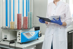 The doctor checks the data in the journal, against the background of petri dishes. Close-up Stock Image