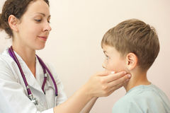 Doctor checks little boy lymph nodes Royalty Free Stock Image
