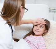 The doctor checks the temperature of a smiling girl Stock Image