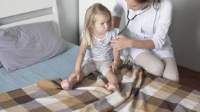 The doctor checks the tummy of the child and listens to the girl with a stethoscope stock video