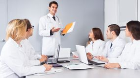 Doctor chief speech at meeting. In office royalty free stock image