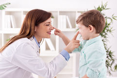 Doctor and child enjoy and playing together touching noses Royalty Free Stock Photos