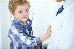 Doctor and child patient. Little boy play with stethoscope while physician communicate with him. Children`s therapy and. Trusting relationship in medicine Royalty Free Stock Images