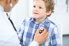 Doctor and child patient. Physician examines little boy by stethoscope. Medicine and children`s therapy concept.  Royalty Free Stock Photos